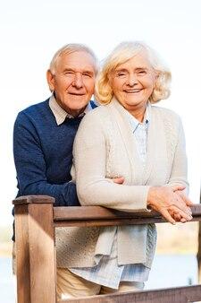 Nós somos felizes juntos. casal feliz de idosos se unindo e sorrindo enquanto fica ao ar livre