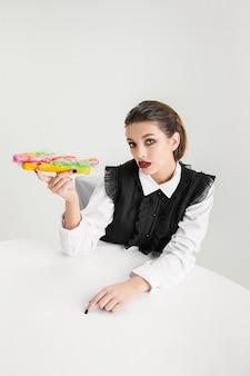 Nós somos o que comemos. mulher comendo cachorro-quente feito de plástico, conceito ecológico