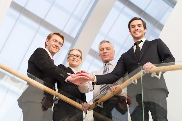 Nós somos os melhores. visão de baixo ângulo de quatro empresários confiantes, próximos uns dos outros e de mãos dadas