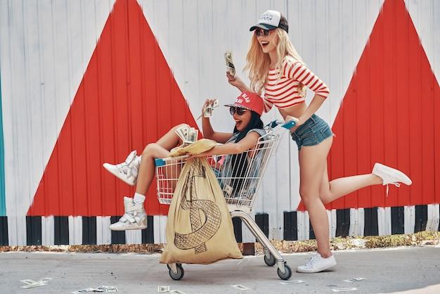 Nós somos ricos! jovens empolgadas segurando uma bolsa de dinheiro e sentadas no carrinho de compras enquanto sua amiga empurra e corre