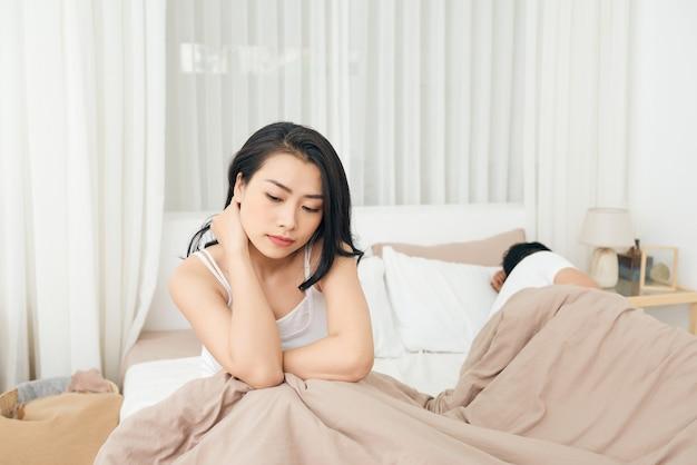 Nós temos um problema. jovem chateada sentada na beira da cama, contra o namorado, deitado na cama.
