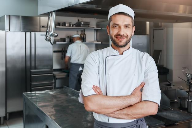 Nós vendemos sabores sorrindo atraente chef cozinheiro com barba em pé com as mãos postas no
