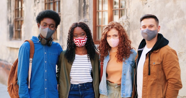 Nossa empresa unidade de melhores amigos usando máscaras de proteção, passando algum tempo juntos na cidade durante ...