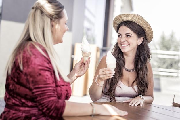 Nossa reunião. mulheres positivas encantadas olhando uma para a outra segurando casquinhas de sorvete