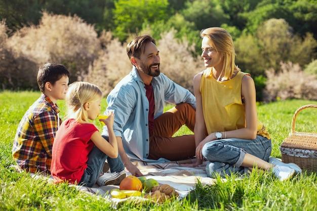 Nossas férias. mãe atraente e feliz sorrindo e fazendo piquenique com a família