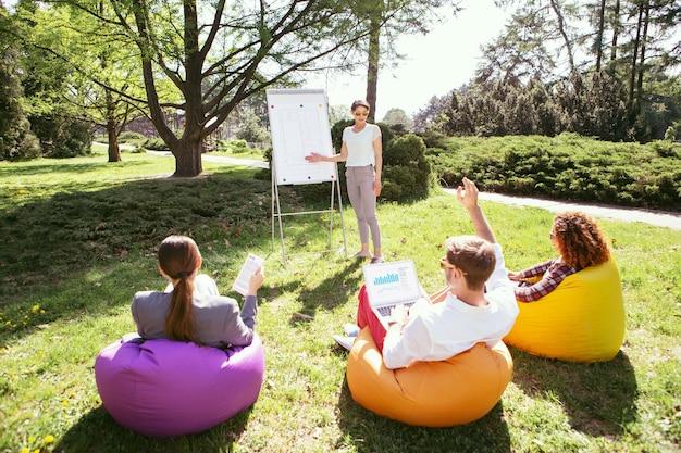 Nosso brainstorming. menina magra concentrada em pé no quadro e discutindo seu projeto com seus colegas de grupo