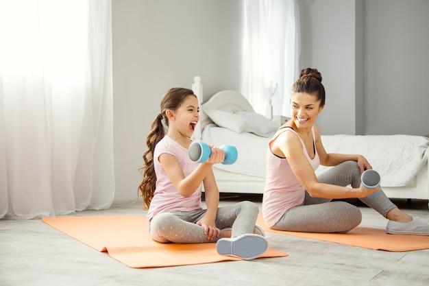 Nosso hobby. linda jovem mãe de cabelos escuros encantada fazendo alguns exercícios com pesos de mão com a filha enquanto está sentada no chão e olhando para sua filha