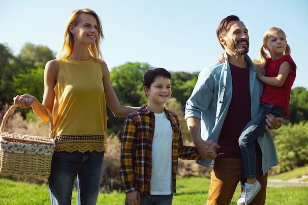 Nosso precioso. homem de cabelos escuros encantado segurando sua filha enquanto passa um tempo com sua família