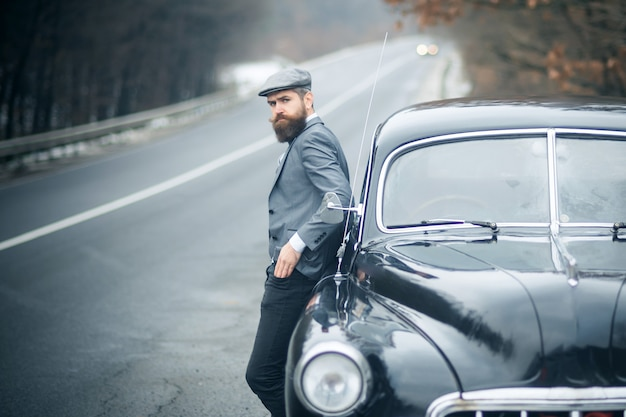 Nostalgia e carro retrô em homem barbudo. cara vintage.