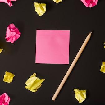 Nota adesiva rosa em branco e lápis rodeado com papel amassado no fundo preto