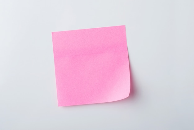 Nota adesiva rosa na parede branca