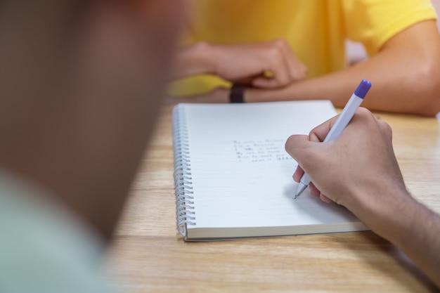 Nota asiática do estudante no caderno ao aprender o estudo e a escrita para o trabalho planeando.