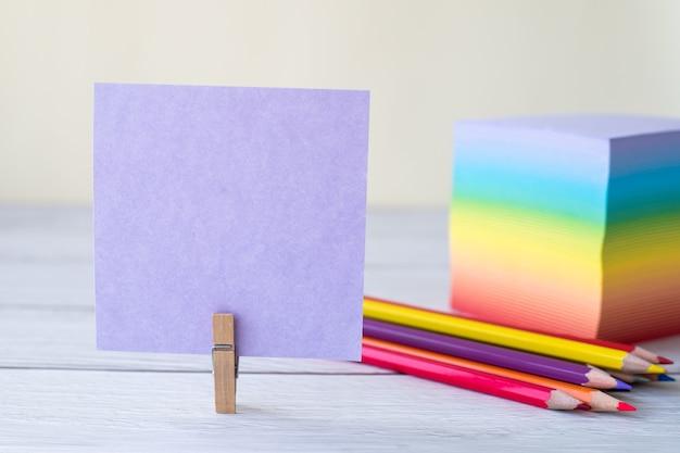Nota auto-adesiva em branco com uma pilha de clipes de lavanderia de caneta de papel colorido colocada na mesa.