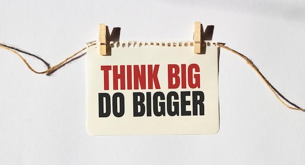 Nota com o texto think big do bigger.