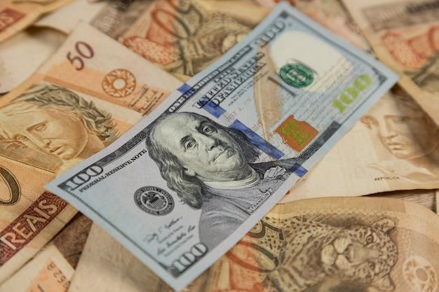 Nota de 100 dólares em cima de notas de 50 reais