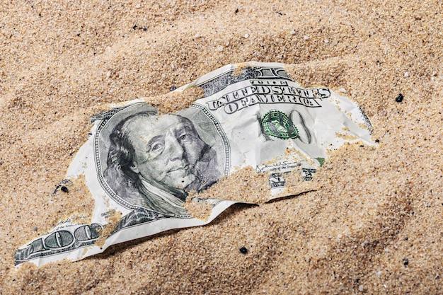 Nota de 100 dólares, enterrada na areia