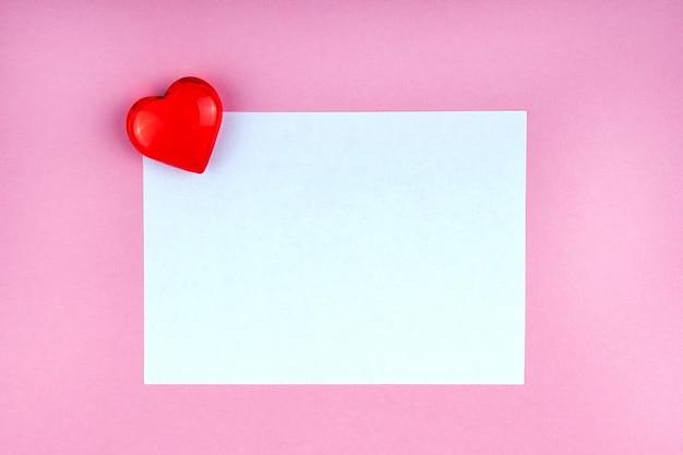 Nota de amor com coração vermelho sobre fundo rosa simulado, copyspace