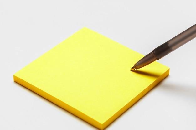 Nota de bloco de notas em branco com caneta close-up