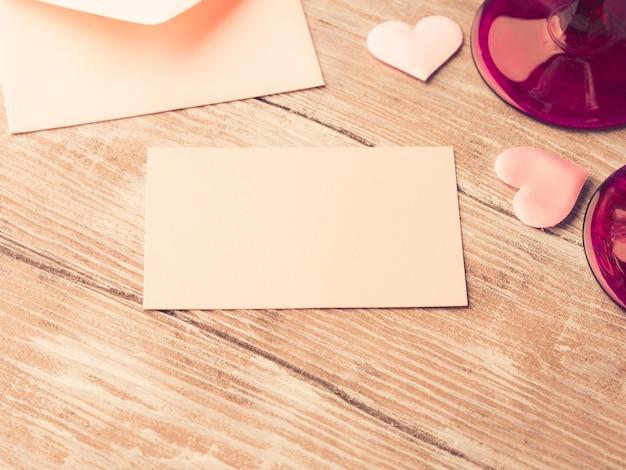 Nota de carta de papel em branco-de-rosa com corações para preencher com seu texto em madeira