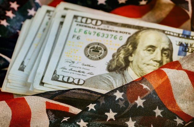 Nota de cem dólares com uma bandeira americana