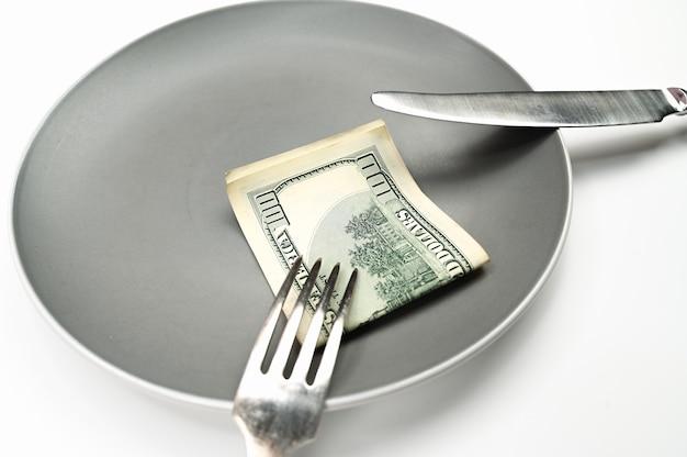 Nota de cem dólares no prato, com garfo e faca no fundo branco isolado. foto de alta qualidade