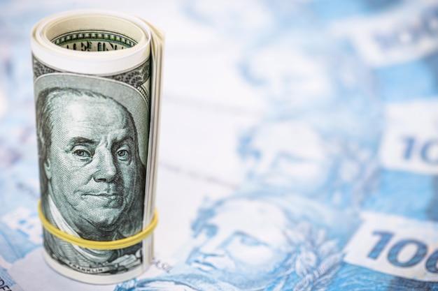 Nota de cem dólares sobre notas de cem dólares, foco do ponto. conceito de desvalorização da moeda brasileira e alta do dólar