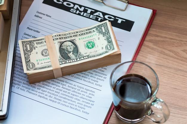 Nota de dólar, café preto, documento de negócios e folha de contato.