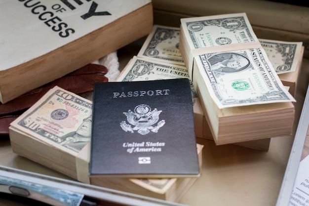 Nota de dólar, passaporte, documento de negócios e chave do livro de sucesso na bolsa.