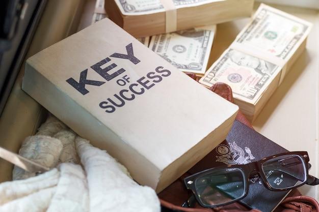 Nota de dólar, passaporte, documento de negócios e chave do livro de sucesso.