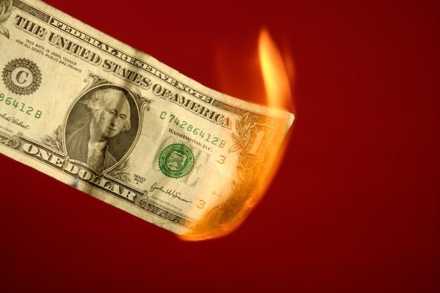 Nota de dólar, queimando em fogo sobre vermelho