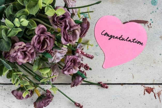 Nota de felicitações no papel de forma de coração com bouque roxo