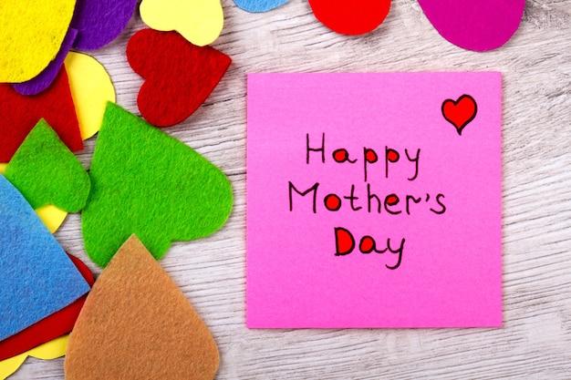 Nota de feliz dia das mães. papel de saudação e corações coloridos. mãe merece amor puro. comemore as suas férias de forma brilhante.
