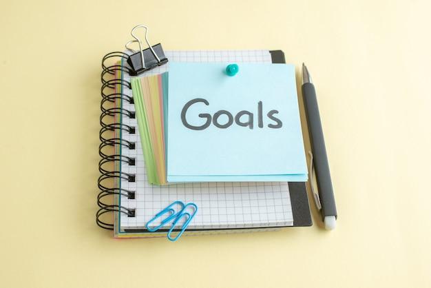 Nota de metas de vista frontal escrita junto com pequenas notas de papel coloridas sobre fundo claro