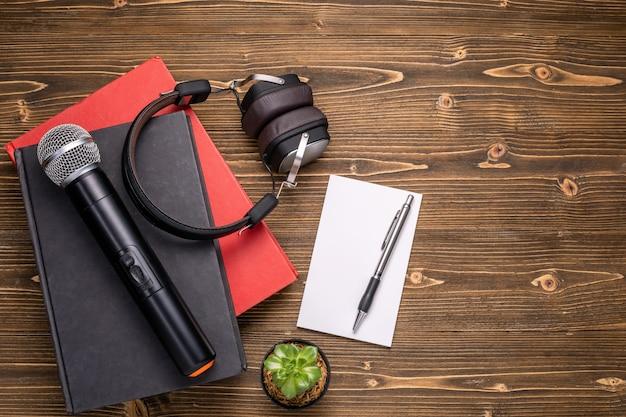 Nota de microfone, fone de ouvido, livro e papel na placa de madeira marrom. aprendendo sobre o conceito de fala