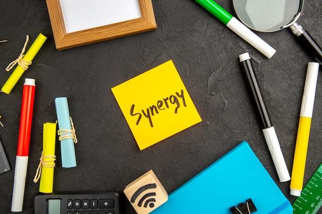 Nota de motivação da vista superior com lápis coloridos e outras coisas na superfície escura