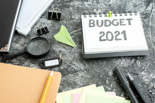 Nota de orçamento de vista frontal com canetas em fundo cinza