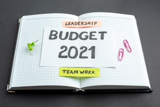 Nota de orçamento de vista frontal em bloco de notas aberto em fundo escuro