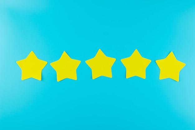 Nota de papel amarela de cinco estrelas no fundo azul com espaço da cópia para o texto. comentários de clientes, feedback, classificação, classificação e conceito de serviço.