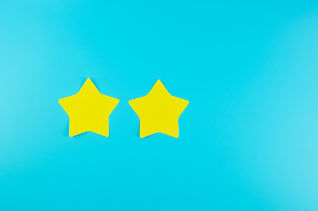 Nota de papel amarela de duas estrelas no fundo azul com espaço da cópia para o texto. comentários de clientes, feedback, classificação, classificação e conceito de serviço.