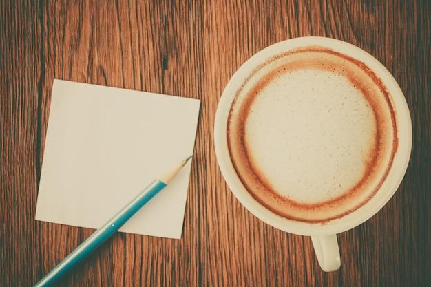 Nota de papel com lápis e xícara de café