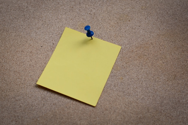 Nota de papel em branco amarelo preso na placa de cortiça com tachinhas brancas, cópia espaço disponível