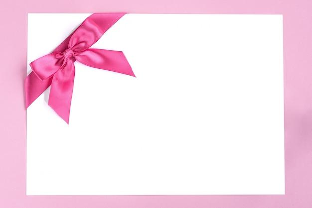 Nota de papel em branco com laço de fita rosa em fundo rosa.
