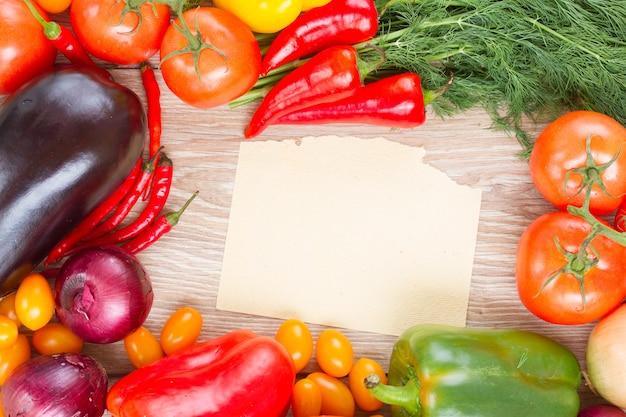Nota de papel em branco com moldura de vegetais coloridos