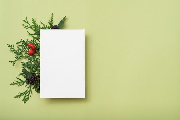 Nota de papel em branco ou cartão com folhas de zimbro, vista superior
