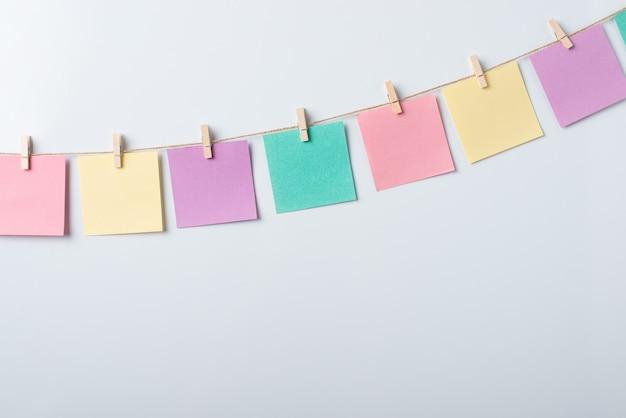 Nota de papel vazio colorido em um fio contra um fundo cinza