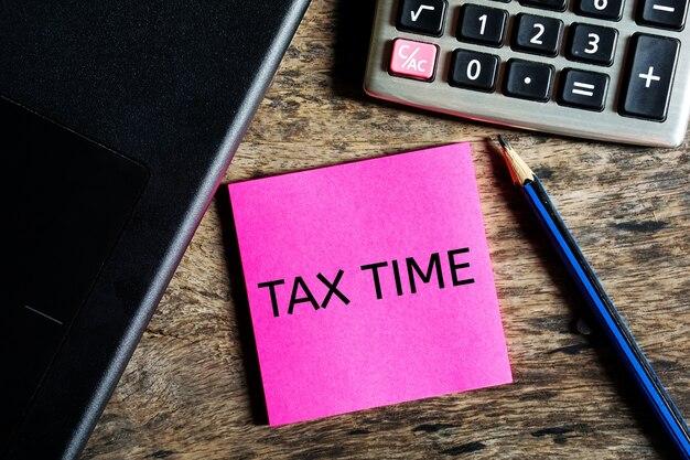 Nota de tempo fiscal com calculadora na mesa