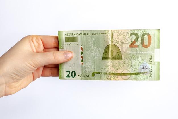 Nota de vinte manat do azerbaijão na mão de uma mulher conceito de pagamento de impostos no final de um ano