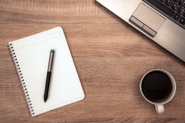 Nota e xícara de café na mesa de trabalho
