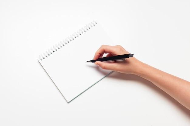 Nota em branco bloco de notas com caneta close-up