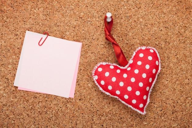 Nota em branco com coração de brinquedo na placa de cortiça de madeira